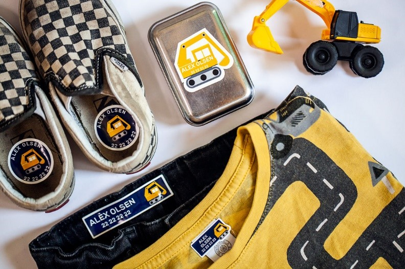 Sko, matboks og klær med navnelapper med gravemaskin på