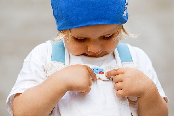 Barn med sekk, lue og navnelapp